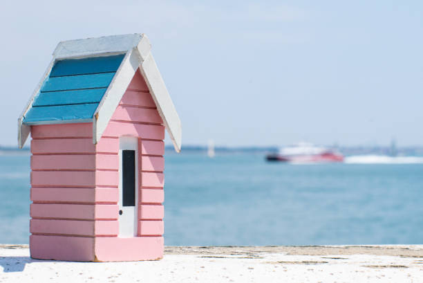 A small wooden model beach hut sat on a wall overloooking the English Channel as a boat goes by A small wooden model beach hut sat on a wall overloooking the English Channel as a boat goes by manche stock pictures, royalty-free photos & images