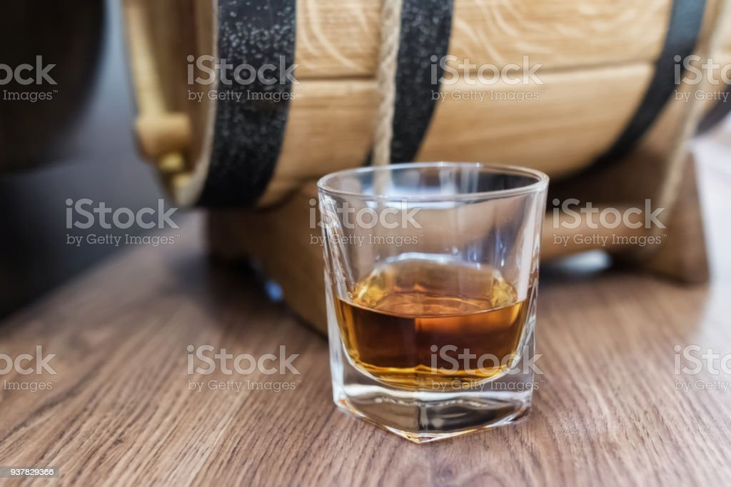 A small wooden oak barrel for home production and a stack of whiskey aged in it stock photo