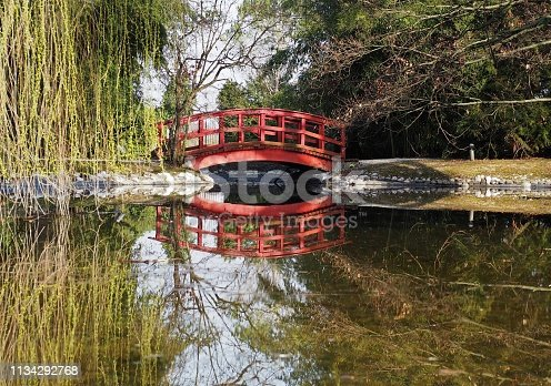 Small wooden red bridge in a woodland with its reflection on a placid river below in first days of springtime.