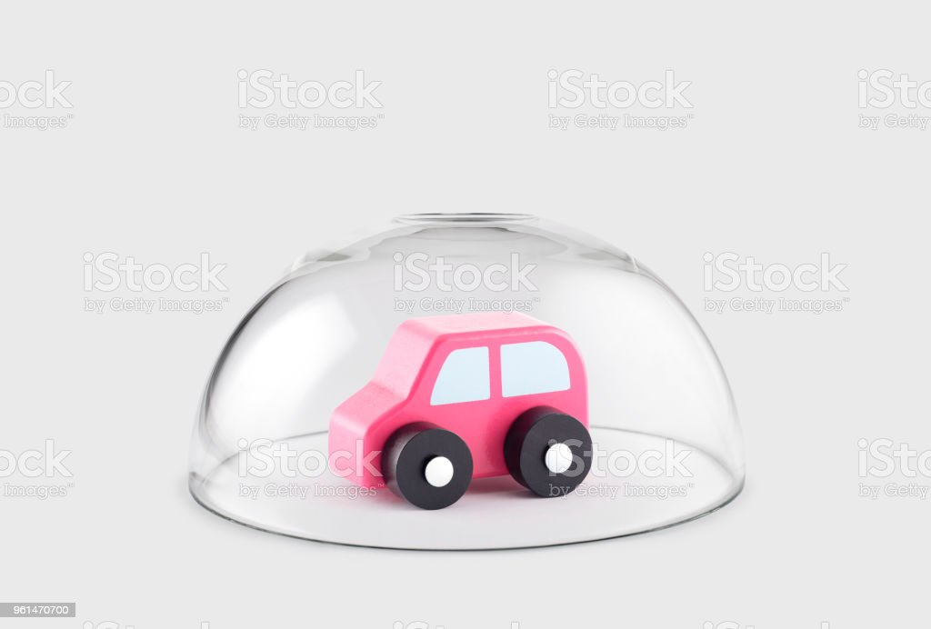 Small wooden toy car protected under a glass dome stock photo