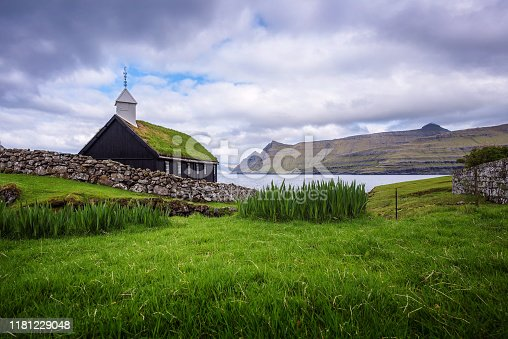 Small black wooden church in the village of Funningur situated on the sea shore. Funningur is located on the island of Eysturoy, Faroe Islands, Denmark