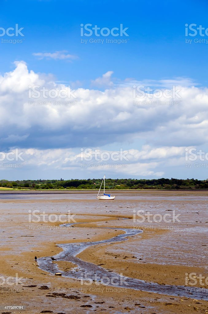 Small yacht at low tide at Mistley, Essex stock photo
