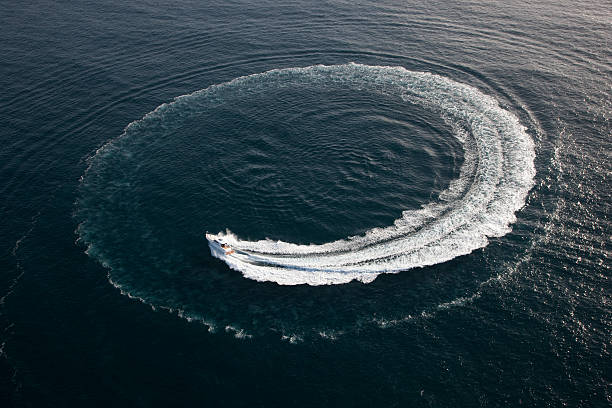 Small yacht making a circle in the water stock photo