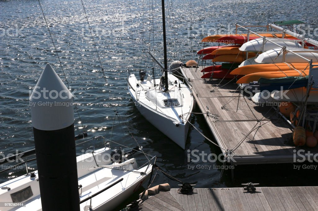 A small yacht moored on a marina with beautiful sunshine on the water stock photo