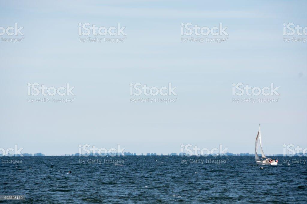 Small yacht sailing at the sea, trees growing on Hel peninsula visible on the horizon stock photo