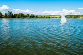 Small yacht sailing on lake with people. Beatiful summer landscape, view from sailing boat. Sunny summer day with nice blue sky, waves on water surface, forest and meadow on the other side.
