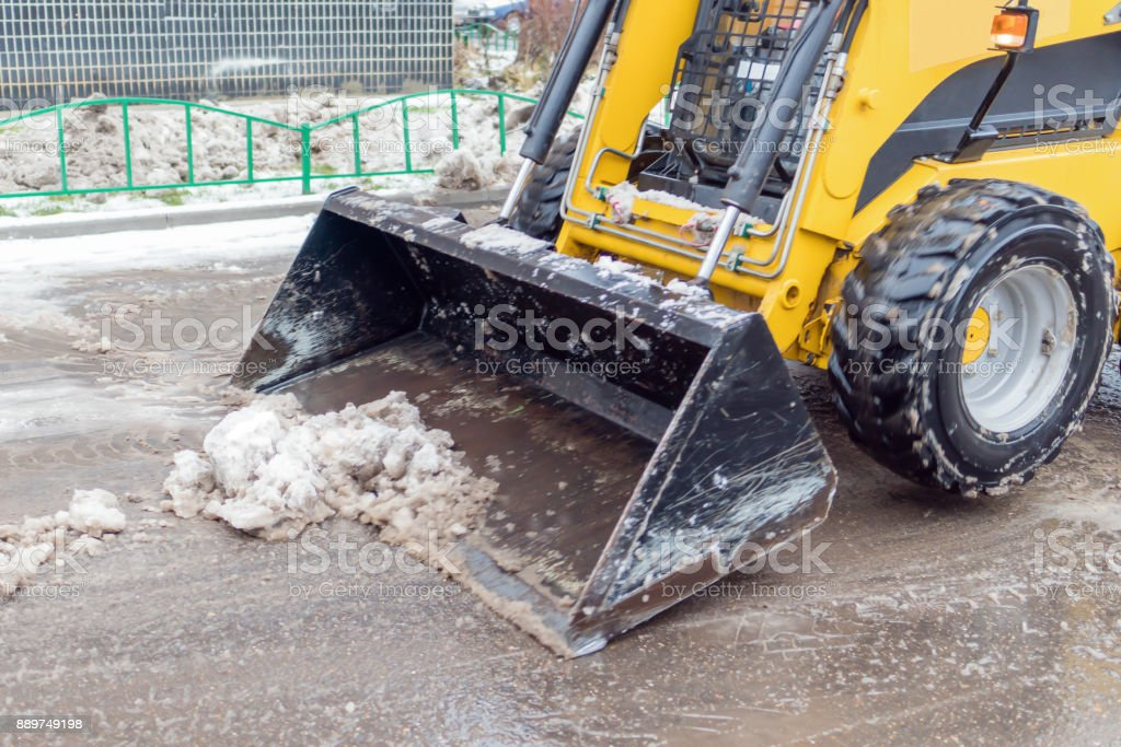 A small yellow bulldozer clears the street from the snow. stock photo