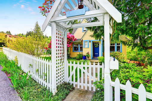 Small Yellow House Exterior With White Picket Fence Stock Photo