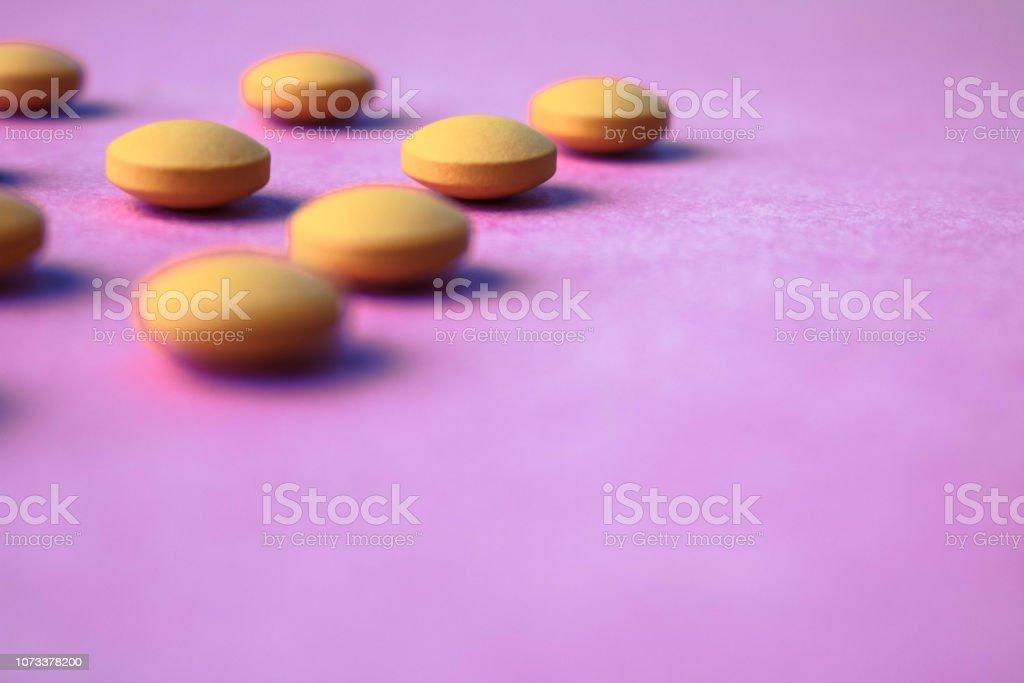 Small Yellow Orange Beautiful Medical Pharmaceptic Round Pills Vitamins Drugs Antibiotics On A Pink Purple Background Texture Concept Medicine Health