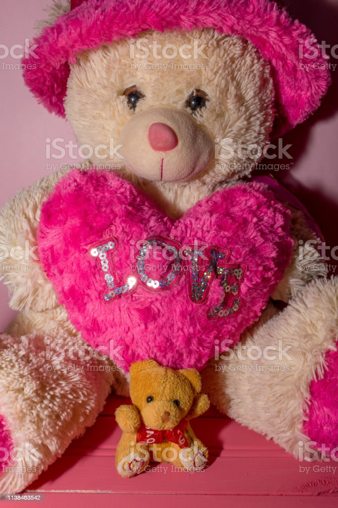 small yellow teddy bear on pink wooden background and heart with word...