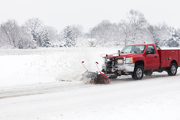 Smaller Truck with Snow Plow Plowing and Country Road stock photo