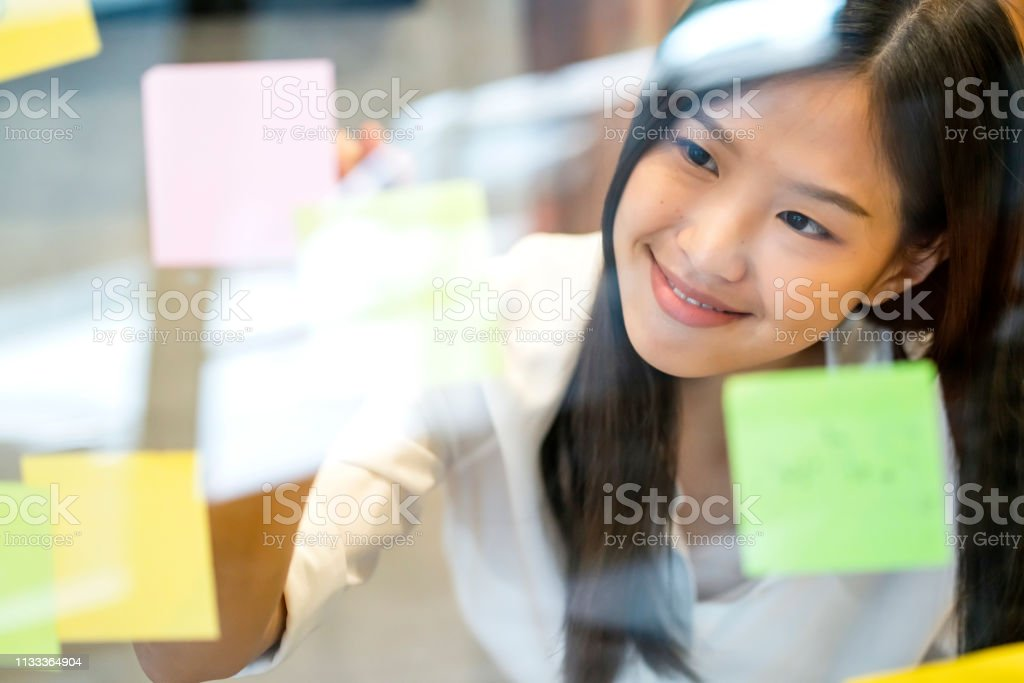 smart active asian businesswoman standing talk to client on smartphone shopfront background with confident and happiness creativity ideas brain storm asian designer post  paper note for new startup project office background Adhesive Note Stock Photo