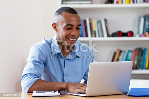 1127582480istockphoto Smart african american businessman with computer 1032531278
