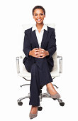 Portrait of a smart African American female executive sitting on office chair with hands clasped. Vertical shot. Isolated on white.