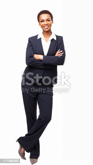 Full length portrait of a beautiful African American businesswoman standing with hands folded. Vertical shot. Isolated on white.