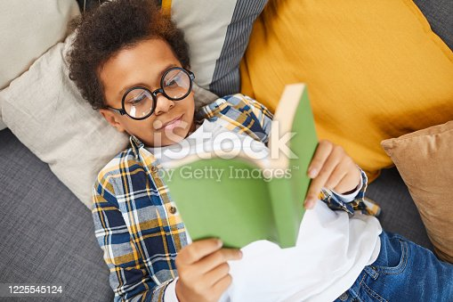 Above view portrait of cute African boy wearing big glasses reading book while lying on couch, homeschooling concept, copy space