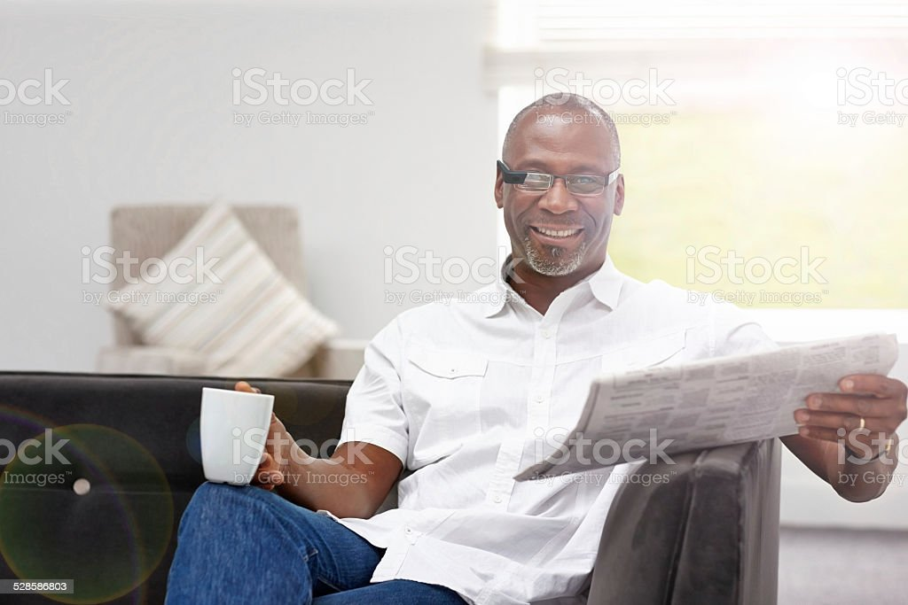Smart african mature man with cup of coffee and newspaper stock photo