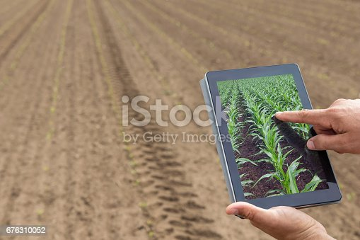 1047941544istockphoto Smart agriculture. Farmer using tablet corn planting. Modern Agriculture concept. 676310052