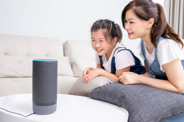 Smart AI speaker concept Smart AI speaker concept - Mom and daughter talk to voice assistant at home and feel happy smart speaker stock pictures, royalty-free photos & images