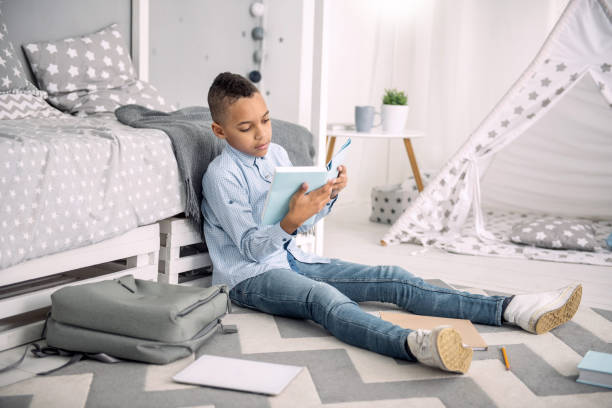 Smart ambitious boy reading book School program. Appealing afro american boy sitting on floor while studying book absentee stock pictures, royalty-free photos & images
