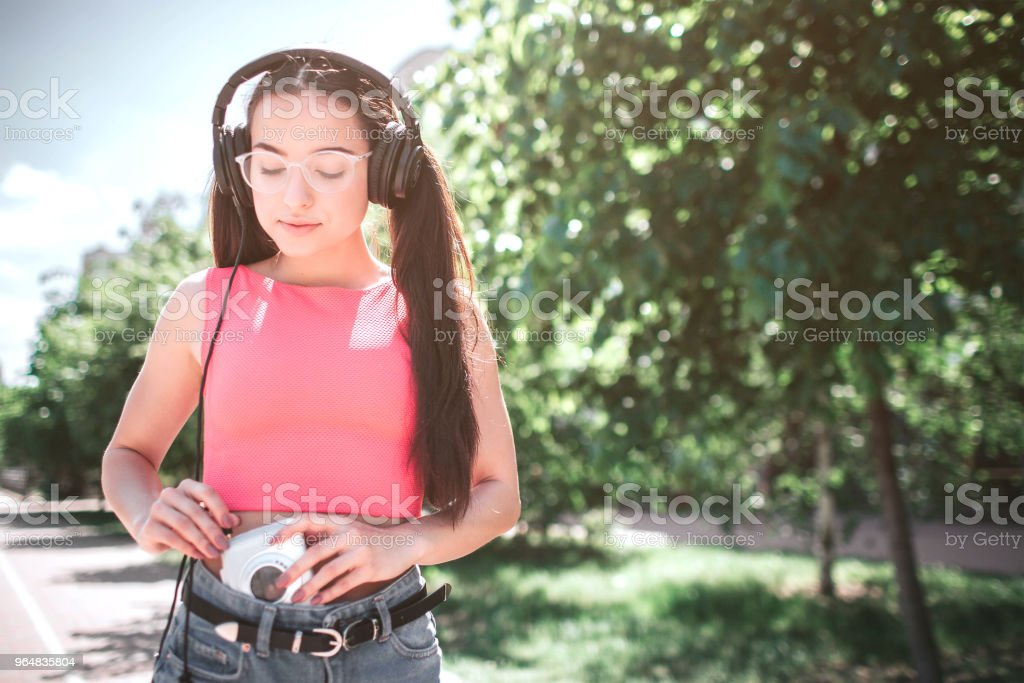 Smart and beautiful girl that likes to listen to music is looking down at the player. She is conecting headphones with white player. Girl is standnig on street royalty-free stock photo