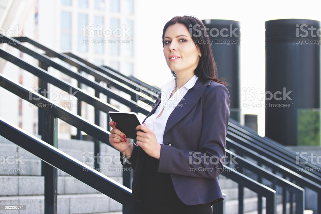 Smart and beautiful. Serious young business woman in smart casual wear carrying digital tablet and looking at camera while standing outside office building. royalty free stockfoto
