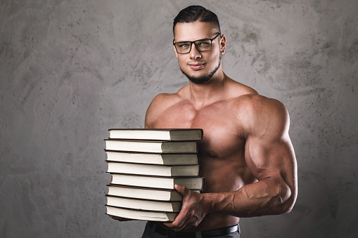 Smart And Muscular Man With A Heap Of Books Stock Photo - Download Image  Now - iStock