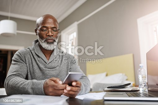 Shot of a senior man using a mobile while working on his finances at home