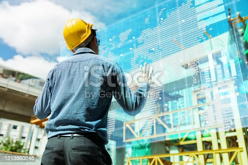 1136415363 istock photo smart asian engineer manager with safety uniform checking site construction with steel and concrete structure background with virtual monitor screen system control 1213860245