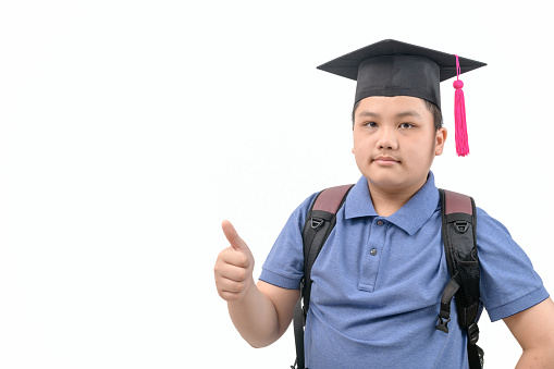 Smart asian student wear graduation cap and showing thumb up and looking at camera isolated on white