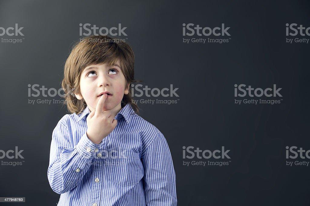 smart beautiful kid thinking against a black background stock photo