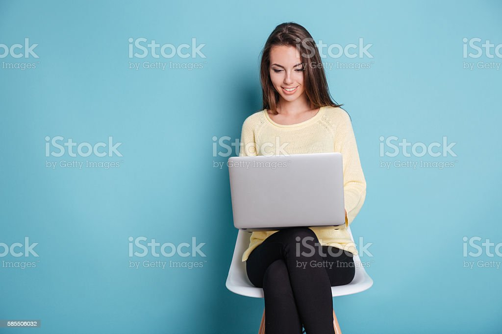 Smart beautiful young girl using laptop over blue background stock photo