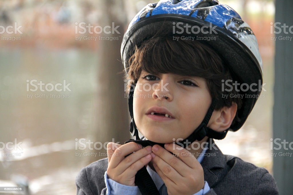 Smart boy opening helmet in a park cycling stock photo