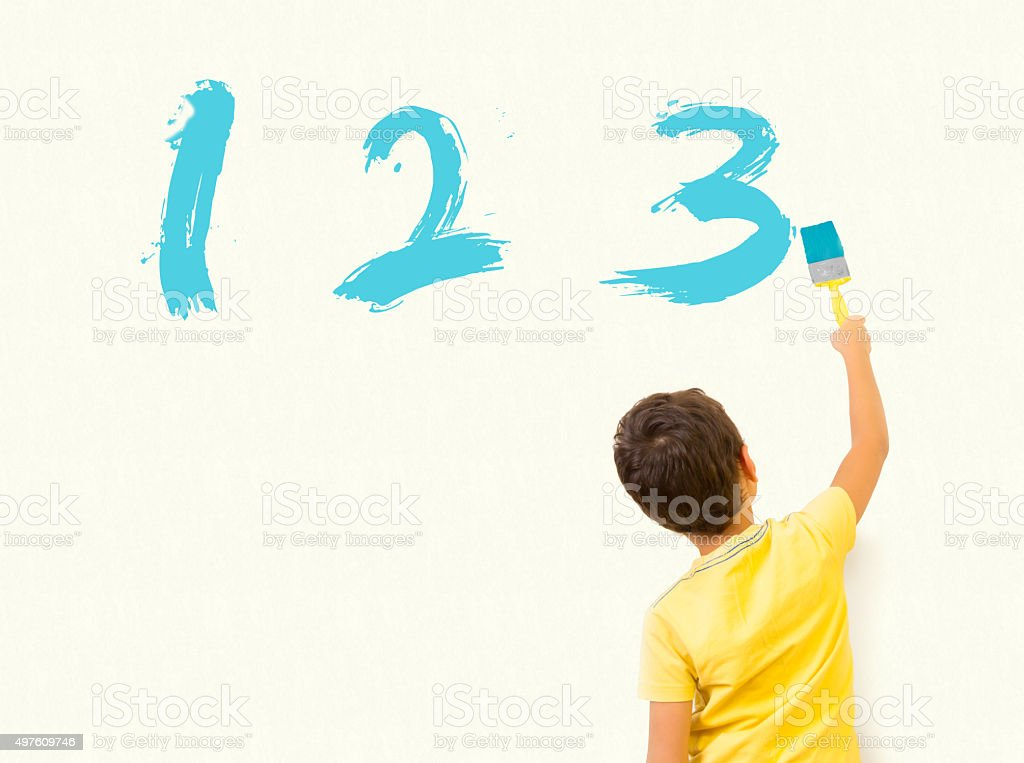 Smart boy painting 123 on the wall stock photo