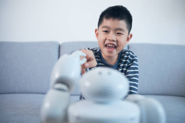 Smart boy touching robot finger indoors stock photo
