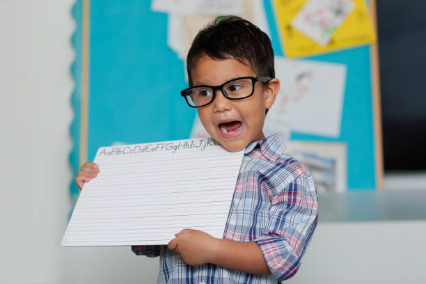 A smart boy wearing reading glasses and speaking or pronouncing words while holding up a blank writing board with a colorful bulletin board in the background. stock photo