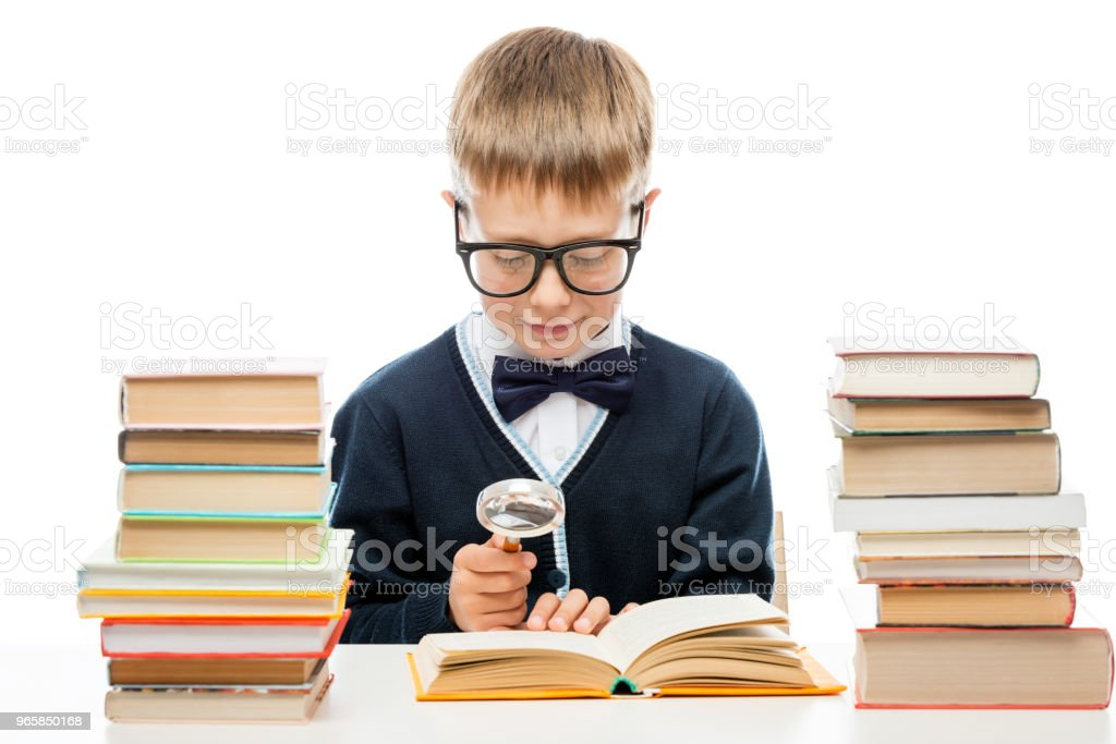 smart boy with glasses with a magnifying glass is considering the text of the book, portrait isolated - Royalty-free Adolescence Stock Photo