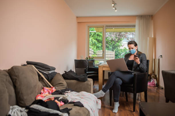 Smart brunette Professional Woman Working From a messy Home Beautiful Brunette Professional Woman Working From a messy Home in her business wear whilst respecting the lockdown due to the corona virus outbreak messy home office stock pictures, royalty-free photos & images