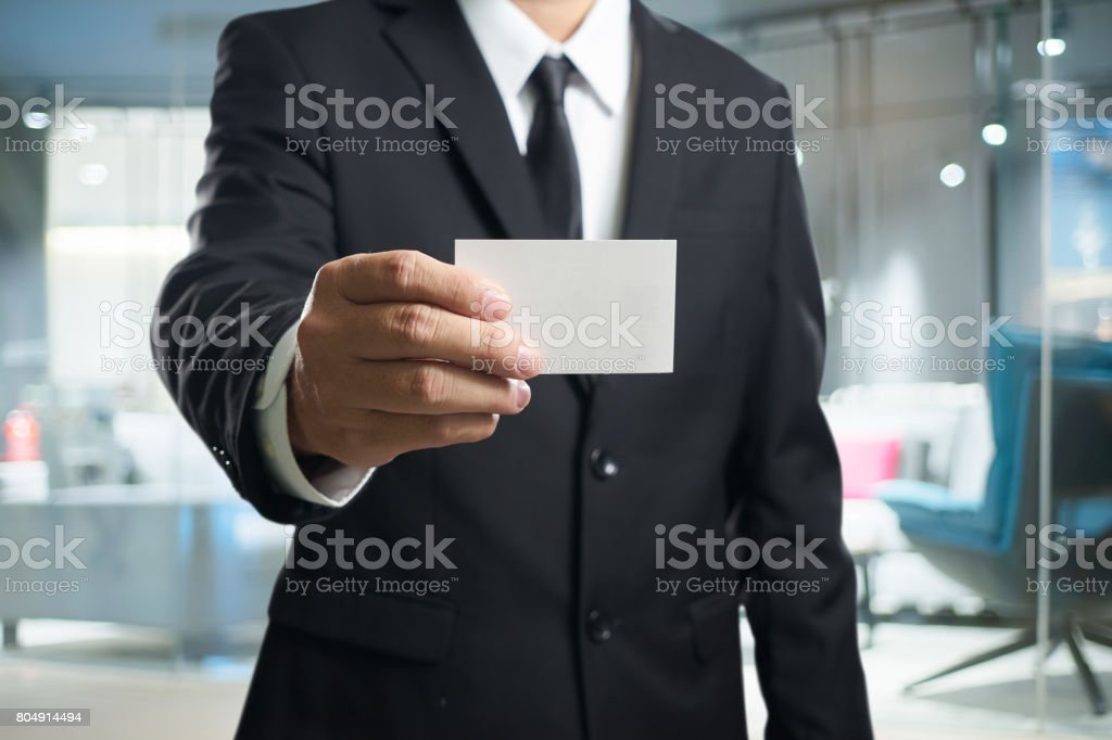 Smart businessman in black suit with show the name card pose .