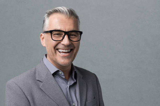 Smart businessman with glasses posing Smart mature businessman with glasses posing on gray background, he is smiling at camera only mature men stock pictures, royalty-free photos & images