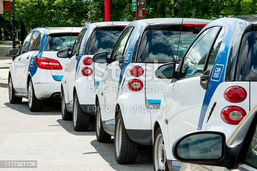 In Vancouver, Canada many Smart Cars with Car2Go branding are parked alongside a downtown street.