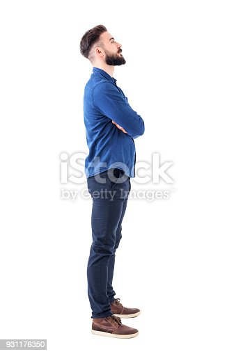 931173966istockphoto Smart casual bearded business man with crossed arms looking up above 931176350
