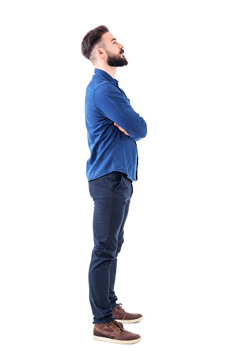 931173966 istock photo Smart casual bearded business man with crossed arms looking up above 931176350