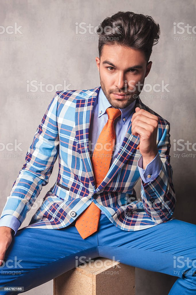 Smart casual business man sitting on a wood box while looking at the...