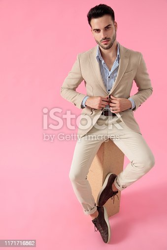 smart casual man fixing coat seated on a wooden box, wearing a suit on pink background; full body, full length