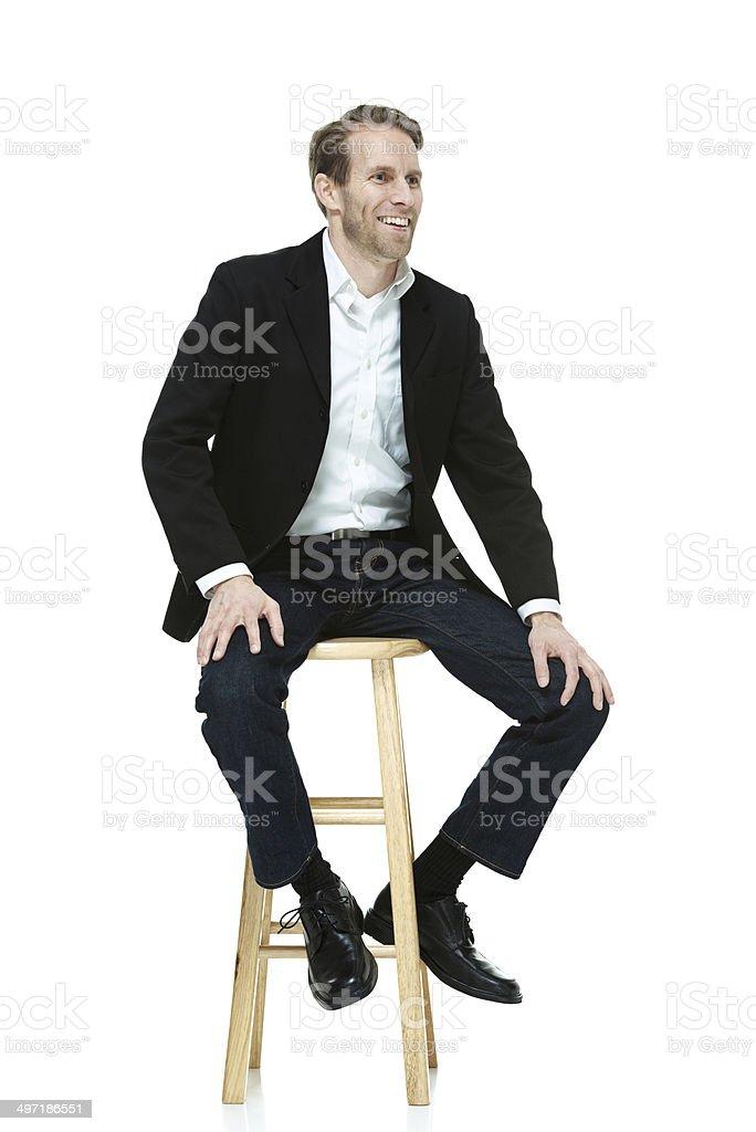 Smart casual man sitting on stool stock photo