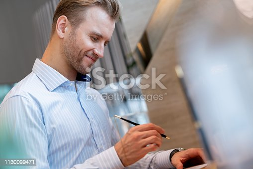 smart caucasian businessman fill decument form on office reception counter