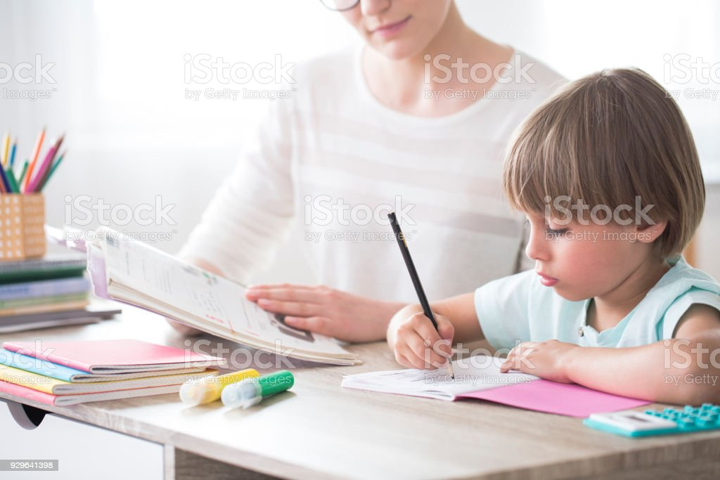 Image of child doing homework - Parents and children doing homework together - Getty Images