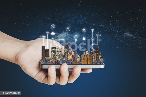 1075752640istockphoto Smart city, building technology and mobile application technology. Hand holding mobile smart phone with buildings hologram and application programming interface technology 1148590433