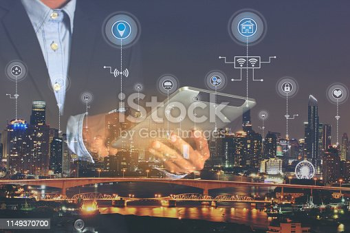 istock Smart city or Internet of Things (IoT), Double exposure of Businessman hands holding digital tablet with icon or hologram on city background, Communication network service and Business concept 1149370700
